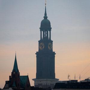 Der Kirchturm vom Michel ragt hoch über die Dächer Hamburgs während die aufgehende Sonne im Hintergrund für ein wunderschönes Farbenspiel sorgt