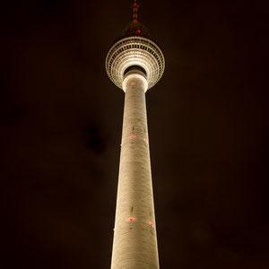 Der Alex ragt in den nächtlich bewölkten Himmel von Berlin