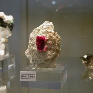 Berilo rojo de 2 x 1 cm de tamaño sobre matriz de riolita