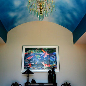 Deep blue sky with misty, white clouds accent this barrel ceiling in a residential foyer.