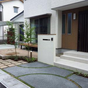 緑がある玄関周り。幅のあるタイル階段を拡張し玄関周りをより広く見せ、リビング前の土の部分では家庭菜園を予定されています。駐車スペースは最小限の2台分とし、残りのスペースをお庭に見立ててゾーニングしています。                                                     岡山市中区 F様邸 フラワーチルドレン エクステリア