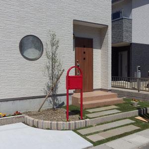 玄関ステップまでのアプローチは舗装し過ぎず、自然石と芝生の目地でナチュラル感を出しています。                         岡山市中区 N様邸 フラワーチルドレン エクステリア