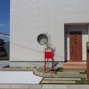 赤いポストと、玄関ドアに色を合わせた角柱に白い表札。初めから施主様がイメージされていた玄関周りのアイデアです。植栽も入り、明るく楽しげなイメージになりました。                             岡山市中区 N様邸 フラワーチルドレン エクステリア