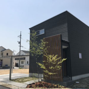 玄関前から家に裏には芝生を張り、シャープな建物に緑でやわかみをプラス。