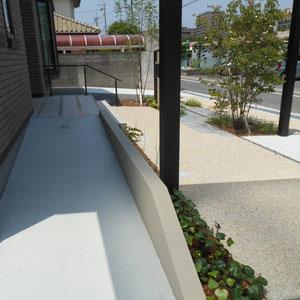 低い塗壁の裏は、駐車場から車椅子で玄関へと向かうアプローチになっています。入口の角を斜めにすることで、少しでも狭さを感じず、衣類のひっかかりを防ぎます。奥に見える手すりも、将来を見据えて新たに取り付けました。              岡山市北区 H様邸 フラワーチルドレン エクステリア
