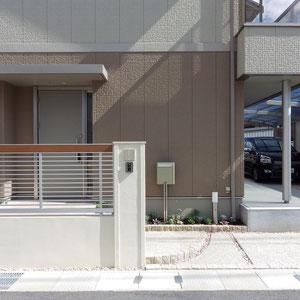 エクステリアの色調は家の外壁との統一感を重視しましたが、アルミフェンス上部にワンポイントだけ木調の横ラインを入れました。転落防止の為のフェンスですが、圧迫感は無く、優しく閉じています。門柱の笠木(コンクリート製)、表札(タイル)、ポストも優しい雰囲気の物が選ばれました。                                                                     岡山市北区 E様邸 エクステリア フラワーチルドレン