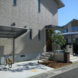 玄関から横に降りている階段は駐輪スペースに伸びています。玄関周りに植栽スペースを取り入れることで柔らかい印象の空間になりました。                                                                                     岡山市南区N様邸 エクステリア フラワーチルドレン