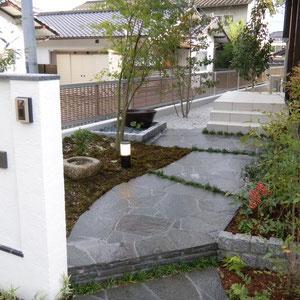 お庭を眺めながらアプローチを通ることのできる和風のエクステリアです。上り口に段差を作ることによって視線が下がり、斜めにすることによって視線が手水鉢の方に向かいます。  岡山市北区O様邸 エクステリア フラワーチルドレン