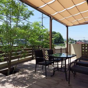 テラスには雨除けの屋根と日差し除けのシェードがついています。遠くに見える緑も借景に取り込み、緑に囲まれた心地よい空間になりました。                                                                                                                                                                倉敷市藤戸町 O様邸 フラワーチルドレン リフォームガーデン