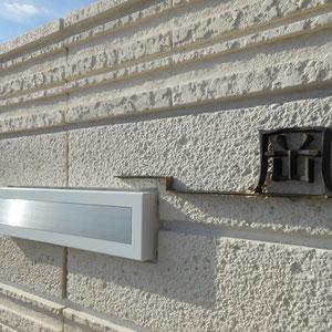 GARE Desighnさんによる真鍮製の表札は、一文字の苗字を支えるようにバーを付け、口金ポストに寄り添うようにデザインしました。背景は、石材を積層したかのようなテクスチャーのあるブロックを選び、ホワイト目地にすることで光の陰影だけによる控えめな肌合いになりました。                                                                                      岡山市北区 O様邸 フラワーチルドレン  エクステリア