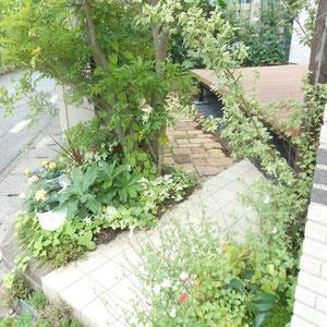 元々あったタイルアプローチに加えて、耐火レンガの小道が加わり、ウッドデッキを取り囲んでお庭をぐるっと歩けるようになりました。後方の隣地堺には、程よく隙間をあけた木樹脂製のアーバンフェンスを立て、トマトやキュウリの家庭菜園スペースとなっています。                                             岡山市中区 K様邸 フラワーチルドレン エクステリア
