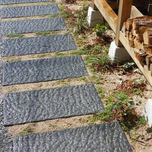 シックなグレー色の舗石は、滑りにくいノミ切り仕上げに。薪置き場の足元をぬうように、ダイカンドラが芽を出してきました。                                          岡山市中区K様邸 ガーデン フラワーチルドレン