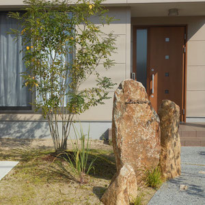 レモングラスやシマカンスゲなどを景石に添えることで、成長した際には野趣あふれる植栽帯ができあがるイメージです。表札も、石と同じく経年変化が楽しめる鉄製の「和錆表札 骨(コチ)」を選びました。                                                         倉敷市福島  Y様邸 エクステリア フラワーチルドレン