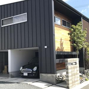 建築で元々備わっていたビルドインタイプのカーポート。外壁とコンクリート、砕石砂利によってグレー系でモノトーンな印象が落ち着きます。