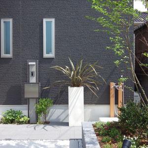 アプローチの床面はコンクリート製の平板、シンプルモダンデザインの機能門柱と、温水も出てシャワー蛇口付きのワンちゃん用ガーデンパンがあります。白いプランターに植えられたドラセナがアクセントになっています。                                                                                     岡山市南区 J様邸 エクステリア フラワーチルドレン