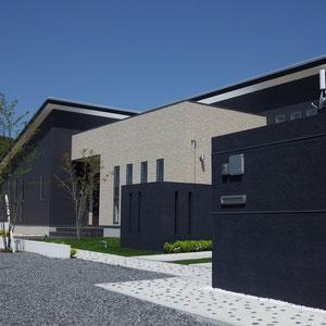 建物を引き立てるシンプルモダンエクステリアです。門塀を含む各ウォールの位置関係、高さを計算してデザインしました。門塀(手前右)にはステンレスバーを埋め込みポイントにしています。アプローチには那智黒石を埋め込み、周り縁を金ゴテで押さえてシャープな印象を出しました。                                          岡山市北区Y様邸 エステリア フラワーチルドレン