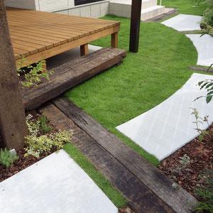 アプローチの素材はコンクリートのハケ引き仕上げと、ポイントに枕木を使用しました。シンプルな素材を選ぶことで芝生が引き立ちます。                                                     倉敷市船穂町 O様邸 ガーデン フラワーチルドレン