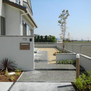 駐車スペース(左)道路からアプローチ(正面下)アプローチ(正面上)と、グラデーションになるようにコンクリート舗装の仕上げを変えています。                     岡山市南区M様邸 エクステリア フラワーチルドレン