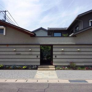 築7年のニ世帯住宅のアプローチと駐車スペース。来客はまず玄関でガラス越しに庭を眺め、それぞれ通されたリビングからも庭を眺めることができる素晴らしい住宅の構成。外構に出来ることは?。ご相談を受けた時は悩みましたが、出した結論は『建築のデザインを邪魔しない。』すなわち『外構のデザインを後でしたように見えないようにデザインする。』という事でした。新築当初からこの外構であったと言っても不思議には思われない仕上がりになったと思います。               岡山市北区 K様邸 フラワーチルドレン エクステリア