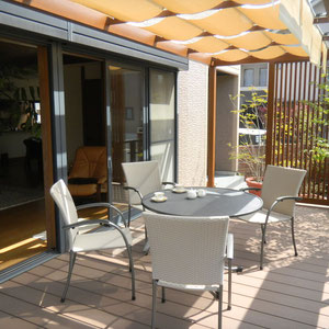 お部屋の中からの続きで、アウトドアリビングになっています。『うち』と『そと』がつながる空間です。イスやテーブル等のガーデンファニチャーの選び方も重要です。色、形、素材等じっくり時間をかけて、その空間に似合うものを選びましょう。  岡山市中区U様邸 ガーデン フラワーチルドレン