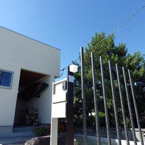 モニュメントのアルミ柱は丸柱。一目で本数が数えられない5本以上にすることで優しい印象が付け加わります。 色はご主人の書斎(入口左の窓)の壁紙に合わせています。                                                               岡山市南区 S様邸 エクステリア フラワーチルドレン