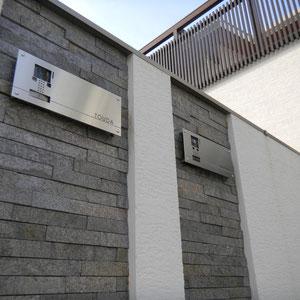 2世帯住宅用の表札周りデザインです。建物で使われているものと同じ天然石貼り材をポイントに使い、特注品のインターフォンカバーを取り付けました。  天然石貼り材を使う時は小口が見えないように壁の厚みを調整することも大切です。今回はインターフォンカバーも塗装の壁より飛び出さないように計算されています。                      岡山市北区T様邸 エクステリア フラワーチルドレン