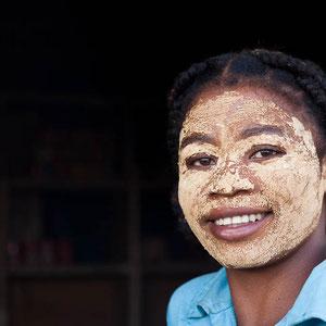 Madagaskar: Junge Frau mit Sonnenschutz (auf einem Stein zermalmte und mit Wasser vermischte Pflanze)