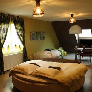 Le grand lit rond de la chambre nature du blockhaus de domleger