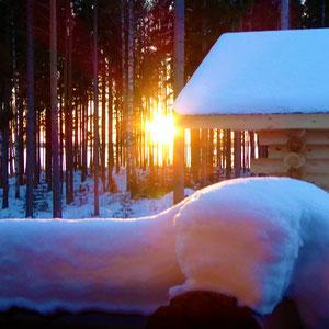 Kehren Sie nach Ihren winterlichen Aktivitäten zurück in die dampfende Sauna mit Blick in das Abendrot und die winterliche Landschaft am See.