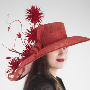Red sinamay hat decorated with hand-made goose feather pompoms.