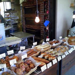 店内。自家製小麦のパンが並ぶ。すぐ後ろにパン焼き釜がある