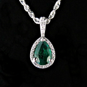 P 95 - 14K white gold pendant with pear shaped emerald surrounded by diamonds.