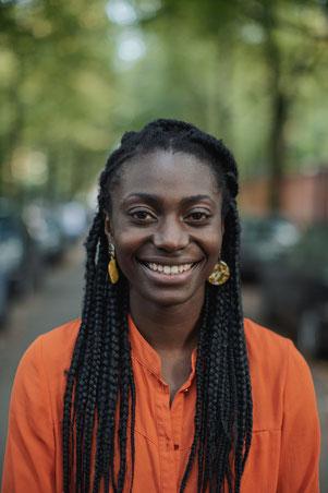 Junge schwarze Frau mit langen Haaren lächelt