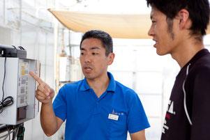 トマトのビニルハウス(下)の灌水(かんすい:水やり)システムの操作パネル / より高度な植物工場へ発展させる試みに取り組んでいる。右は、このシステムの開発管理をしている伊原さん。