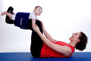 Mutter liegt auf dem Rücken. und streckt die Beine in die Luft. Ihr Baby ist mit einem Gurt an den Beinen der Mutter gesichert. Dabei Trainiert die Mutter ihren Körper. Beide haben Spaß.