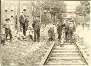 Eisenbahner und George Pellissier (Mitte links) stehen neben einem Thermit-Tiegel vor der Entzündung bei der Verlegung der ersten Gleise in den Vereinigten Staaten mit der Thermit-Schweißtechnik im August 1904