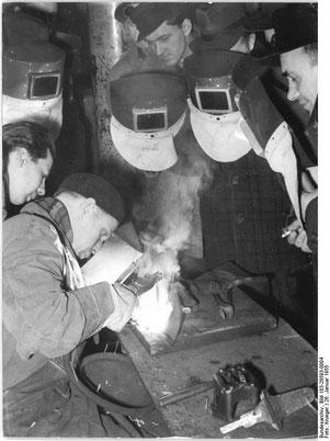 Interessiert beobachten die Kollegen der verschiedenen MTS-Werkstätten des Kreises Nauen am 26. Januar 1955, wie Schweißermeister Ortmann von der Schweißtechnischen Versuchs- und Lehrwerkstatt Berlin-Adlershof  nach der Nasarow-Methode schweißt