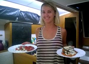 Hostess bei Yacht-Urlaub serviert Vor- und Hauptspeiße
