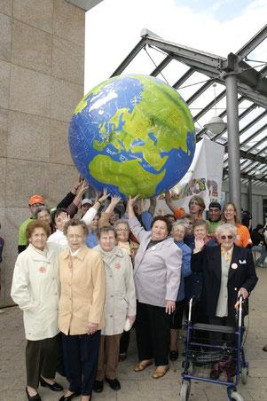 """Seniorinnen """"tragen"""" gemeinsam mit Pastor Robert Schumann die Welt auf ihren Händen beim Lauf für Frieden und Toleranz 2008"""