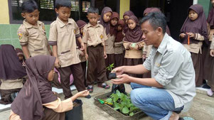ポットでの苗の育て方をコーディネーターから学ぶ子どもたち