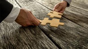 Lösungen suchen in der Politik: Zwei Hände reichen sich zwei passende Puzzle-Teile