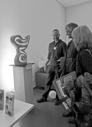 """Markus Brinker mit interessierten Besuchern bei der Präsentation der Holzskulptur """"Kundalini"""""""