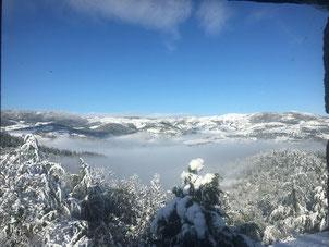 Une vallée montagnarde en ardéche enneigée avec un tapis de brouillard, vue de la terrasse du gite de la gorre à louer en ardeche