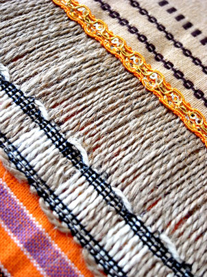 Close-up of  natural jute joining ribbon on orange, white and sandy striped, flat-weave, Indian cotton throw