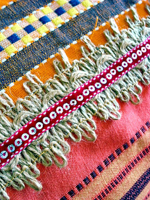 Close-up of natural jute and burgundy sequence joining ribbon on three-piece, red, orange and pink striped, flat-weave, Indian cotton throw