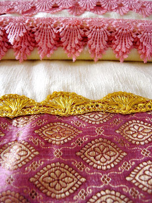 Close up of gold ribbon and pink lace on joined, cream velveteen & grape-coloured silk brocade Indian throw