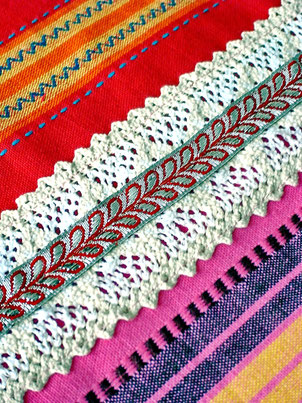 Close up of ivory lace and silver ribbon, joining three-pieces of pink, orange and red striped, flat weave, Indian cotton throw