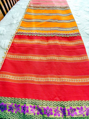 Three-piece, red, orange and pink striped, flat-weave, Indian cotton throw with natural jute and burgundy sequence joining ribbon and thick, floral, maroon and gold jari border with cream pom-pom trim