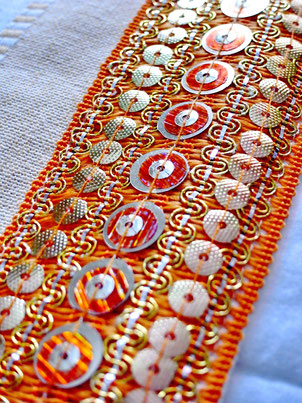 Close-up of orange/metallic sequence joining ribbon on three-piece, orange, white and sandy striped, flat-weave, Indian cotton throw