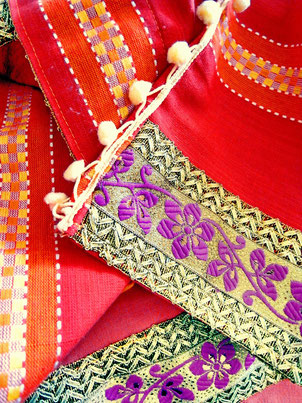 Close up of thick, floral, maroon and gold jari border with cream pom-pom trim on three-piece, red, orange and pink striped, flat-weave, Indian cotton throw